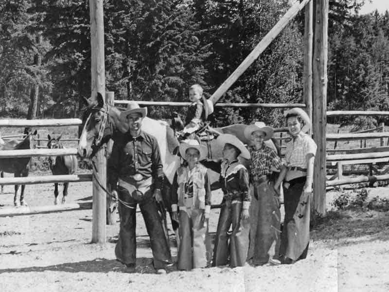 Black and white photo of a man, woman and four boys dressed in western wear standing in front of a horse at Flathead Lake Lodge.