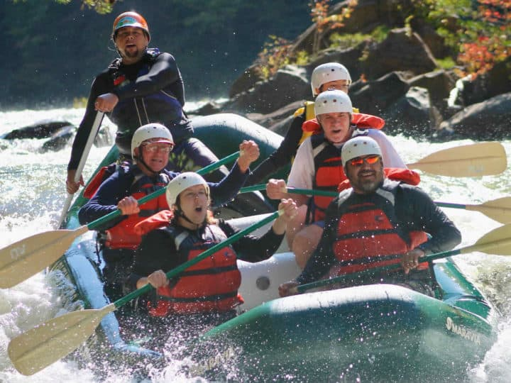 7 people in a raft riding through a rapid on the Ocoee River in Tennessee