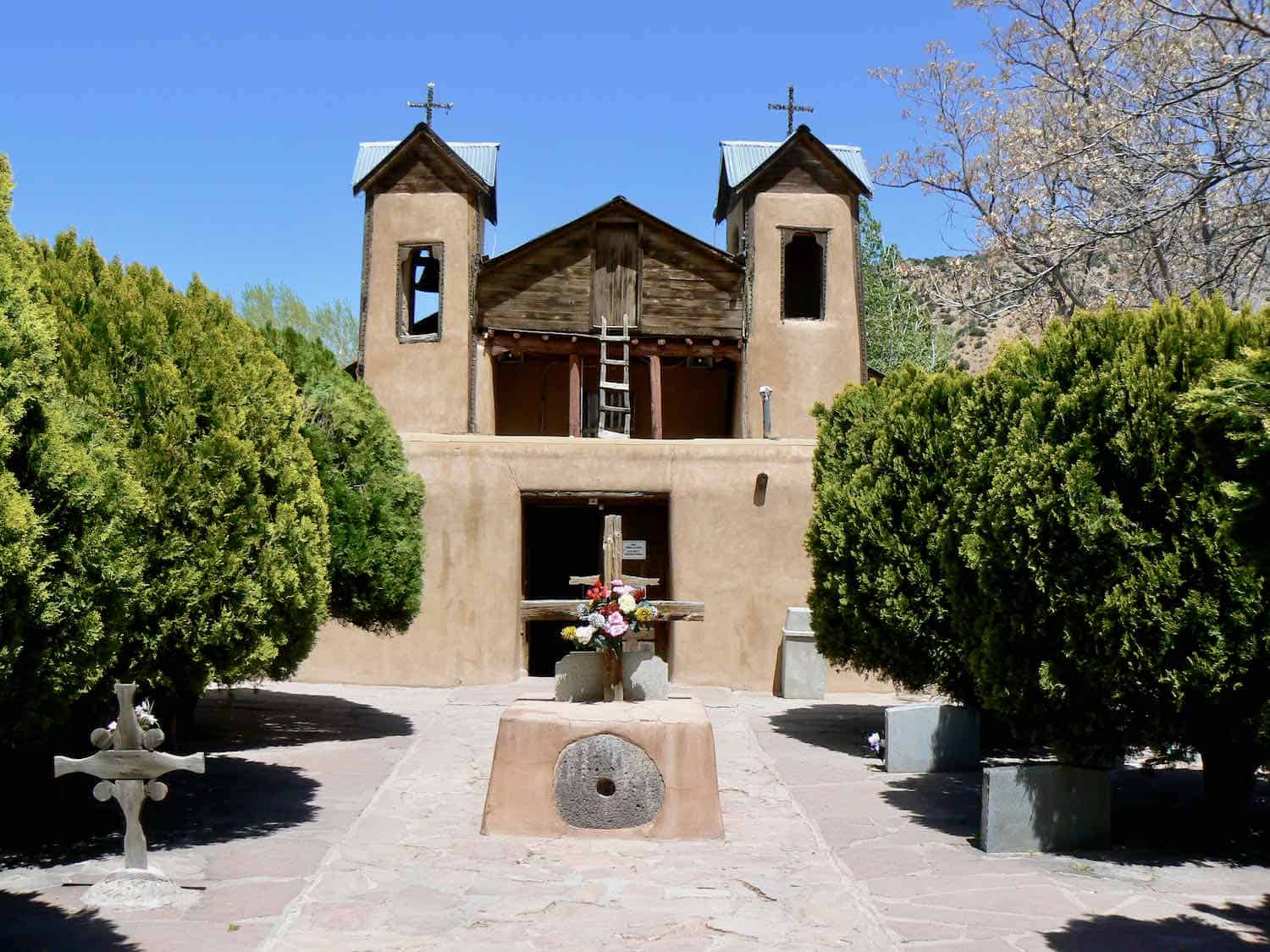 An adobe church in the Spanish Colonia style flanked by a row of evergreen trees on each side.