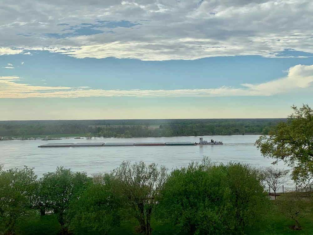 a barge traveling down the Mississippi River with green trees on both banks