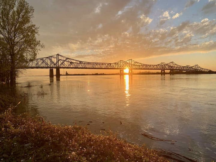 bridge over a wide river with an orange sunset